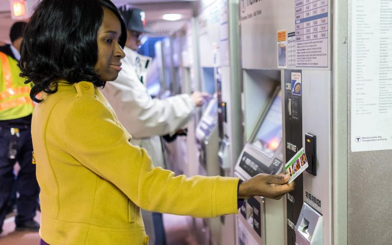 A woman taps her card on a fare vending machine to add value
