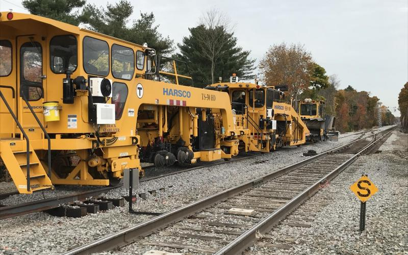Track surfacing equipment will tamp down the stone ballast and spread it evenly around the tracks