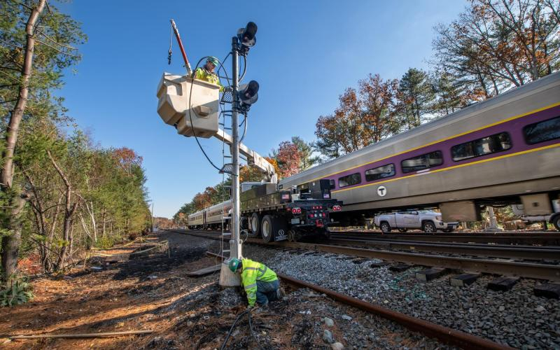 A crew works on signal upgrades in Weston as a Commuter Rail train passes by