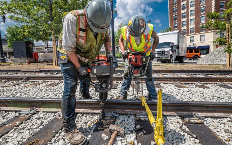 Crew members aligning rail and replacing rail ties on the Green Line C