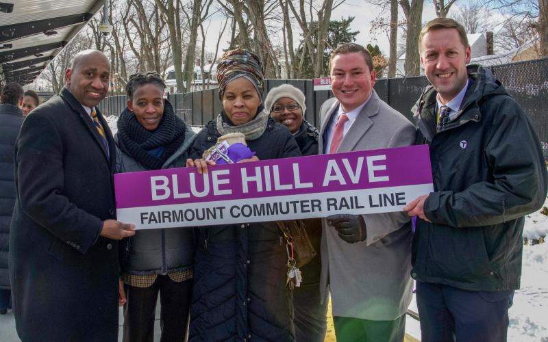 A group of communitiy advocates and MBTA General Manager Steve Poftak pose on the platform with a new station sign.